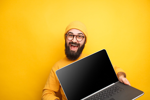istock Smiling hipster in glasses posing with laptop 1094980690