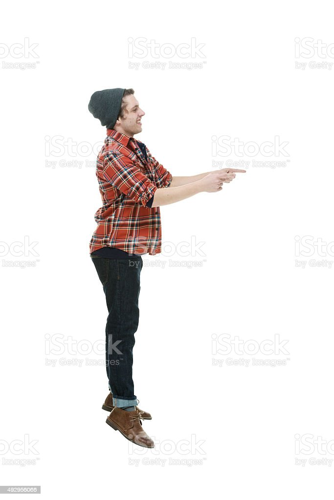 Smiling hipster jumping and pointing away stock photo