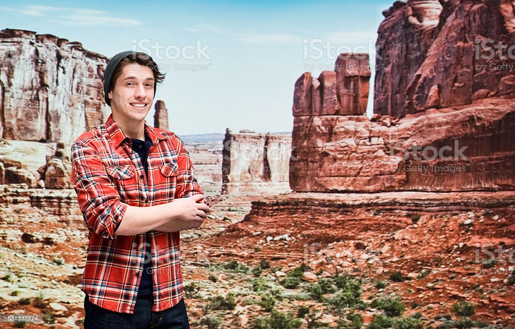 Smiling hipster standing at the mountain stock photo