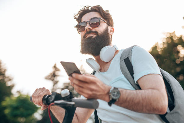 Smiling hipster with gadget riding electric scooter stock photo