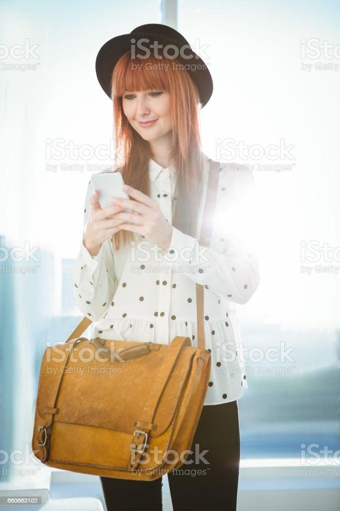 Mensagens de mulher hipster sorridente com seu smartphone - foto de acervo