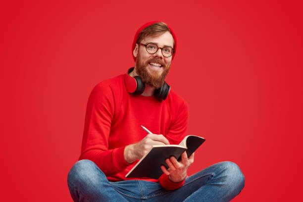 sourire de hipster écrivant dans le cahier - fond couleur uni photos et images de collection