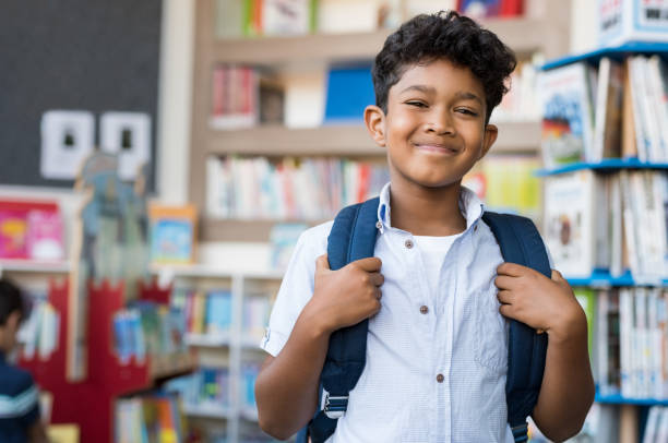 Smiling hispanic boy at school Portrait of smiling hispanic boy looking at camera. Young elementary schoolboy carrying backpack and standing in library at school. Cheerful middle eastern child standing with library background. 8 9 years stock pictures, royalty-free photos & images