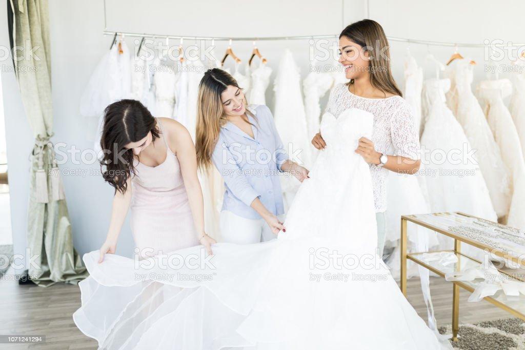 Smiling Hispanic Bride Trying Elegant Wedding Dress Stock