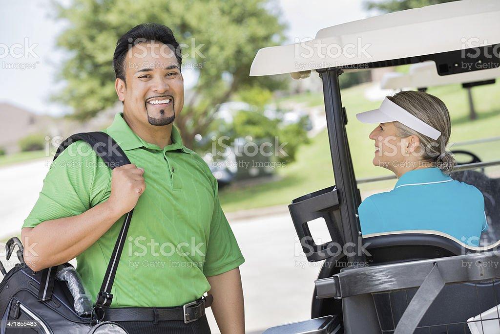 Smiling Hispanic businessman loading golf clubs into cart royalty-free stock photo