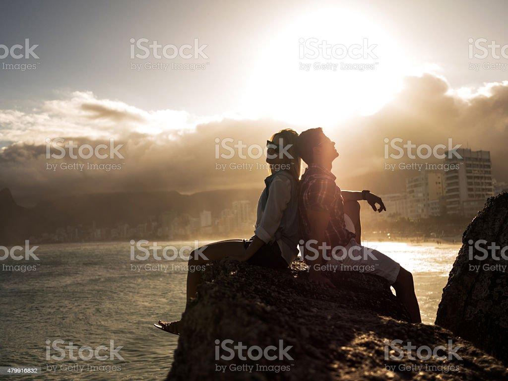 Smiling Hispanic couple sitting back to back on a rock. stock photo
