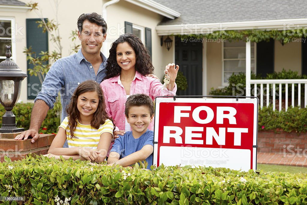 Smiling Hispanic family of four next to home for rent sign stock photo