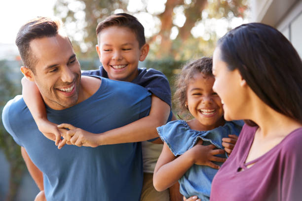 Smiling Hispanic Family With Parents Giving Children Piggyback Rides In Garden At Home stock photo