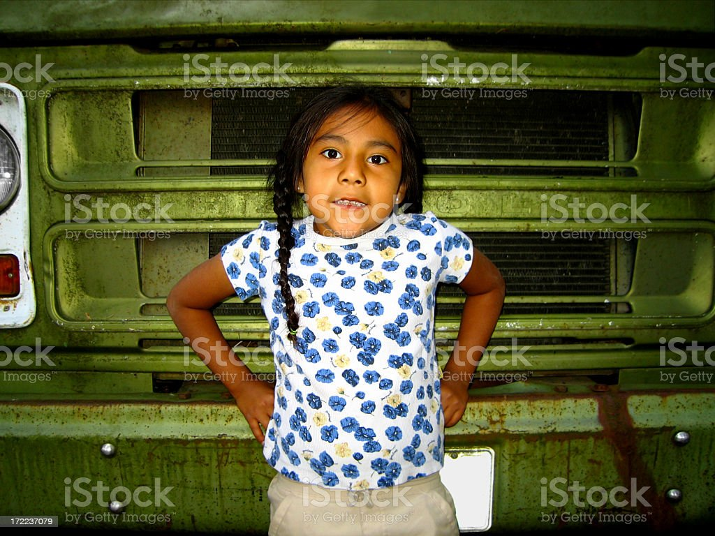 Smiling Hispanic girl on the front of dirty old green truck stock photo
