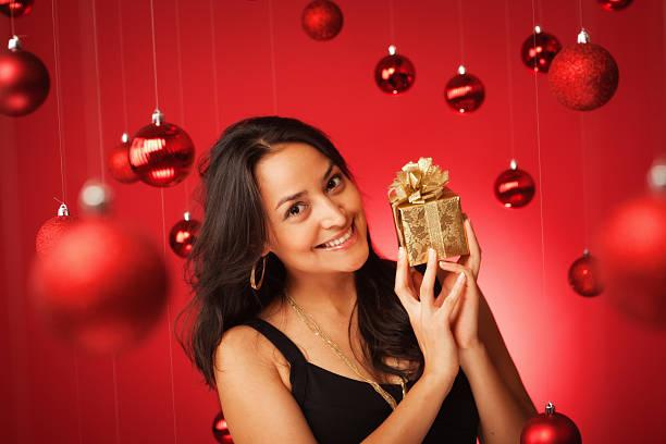 lächelnde hispanic modell im schwarzen kleid mit weihnachtsgeschenk hz - goldgefüllte kette stock-fotos und bilder