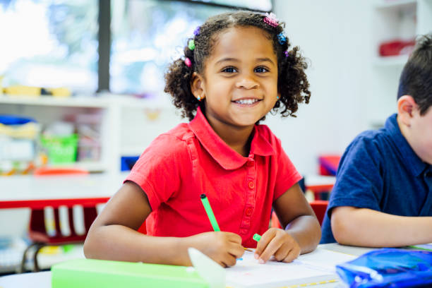 Smiling Hispanic schoolgirl drawing in the classroom stock photo