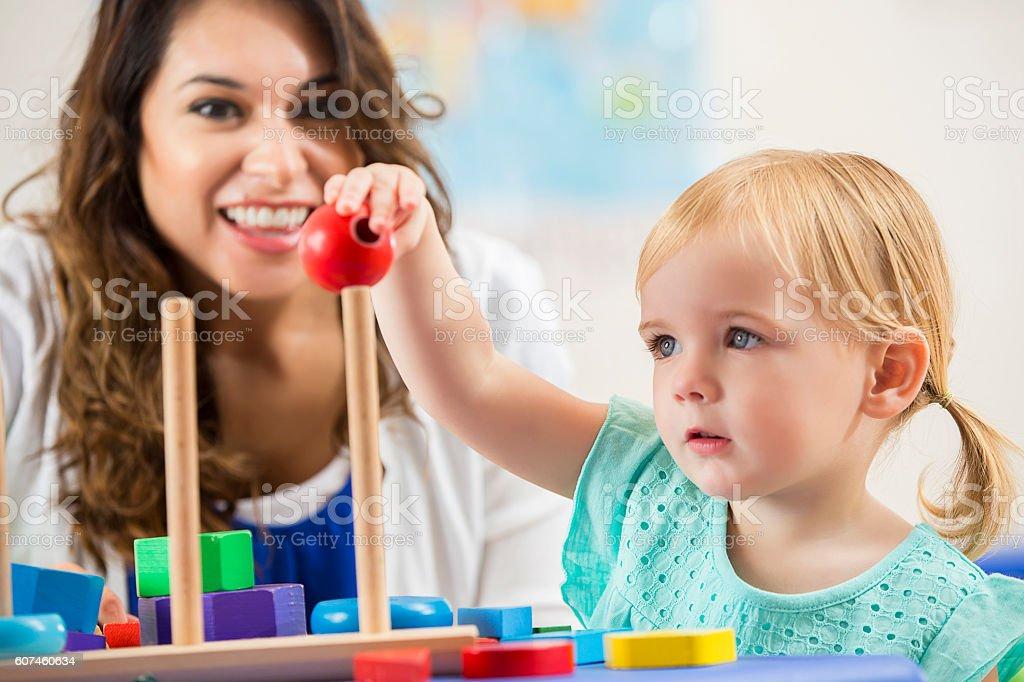 Smiling Hispanic teacher working with cute preschooler stock photo