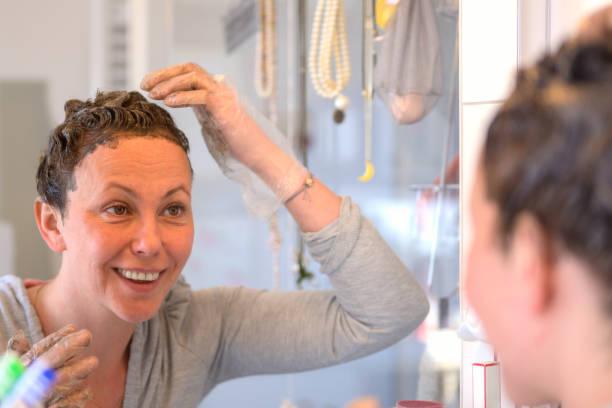Smiling Hispanic woman applying hair dye stock photo