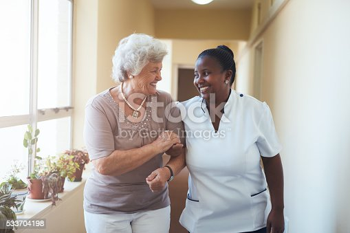 istock Smiling home caregiver and senior woman walking together 533704198