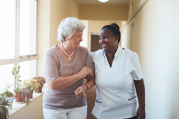 Smiling home caregiver and senior woman walking together Portrait of smiling home caregiver and senior woman walking together through a corridor. Healthcare worker taking care of elderly woman. dignity stock pictures, royalty-free photos & images