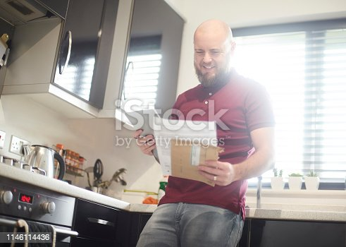 Home owner reading paperwork and financial figures on digital tablet