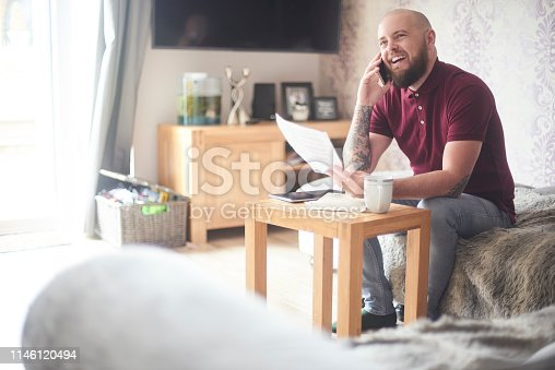 Home owner sat on the sofa in his living room smiling as he talks on the phone