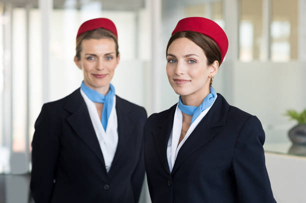 Smiling hostess at airport Two airhostess in uniform at airport looking at camera. Flight attendants standing together in blue and red uniform. Portrait of smiling young hostess ready for flight. cabin crew stock pictures, royalty-free photos & images
