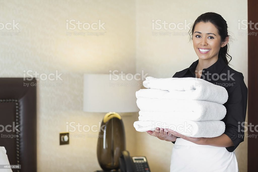 Smiling hotel maid holding pile of fresh towels stock photo