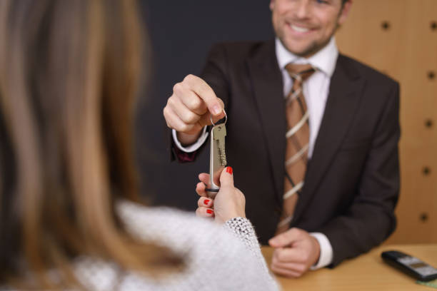 Smiling hotel manager handing over a door key stock photo
