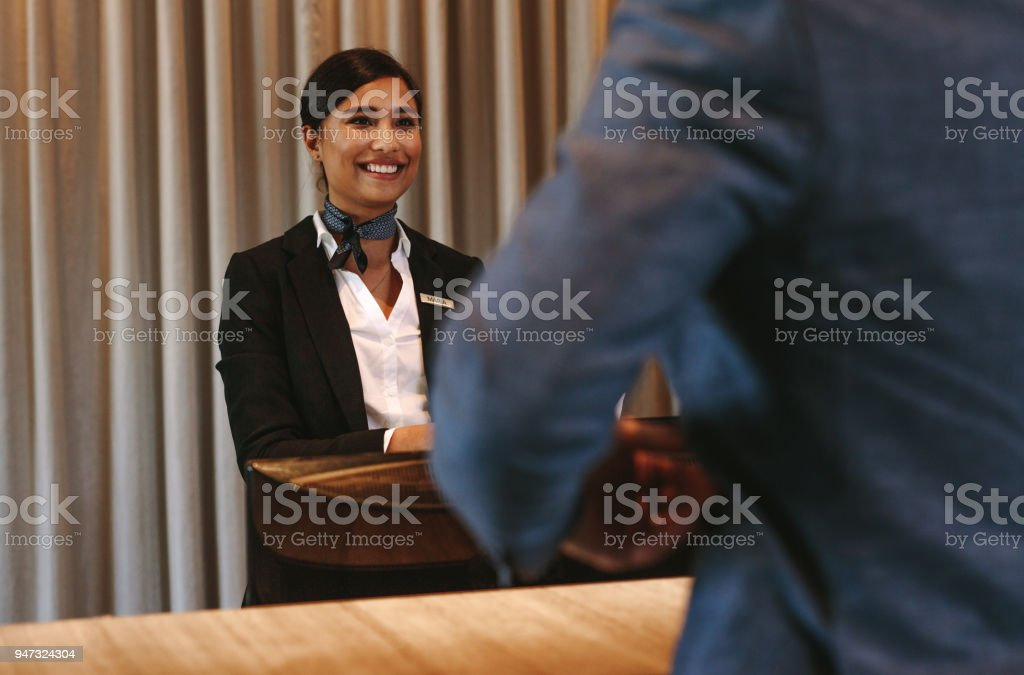 Smiling hotel receptionist attending guest at check-in counter stock photo