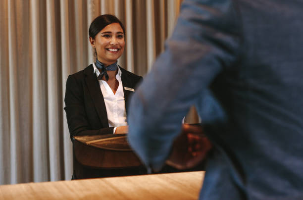 Smiling hotel receptionist attending guest at check-in counter Smiling hotel receptionist talking with male guest at reception counter. Happy female receptionist worker standing at hotel counter with businessman checking in. concierge stock pictures, royalty-free photos & images
