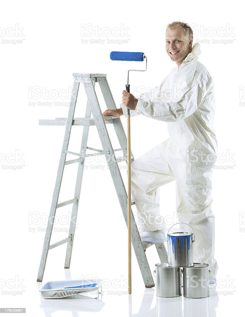 Smiling house painter with paint roller and ladder stock photo