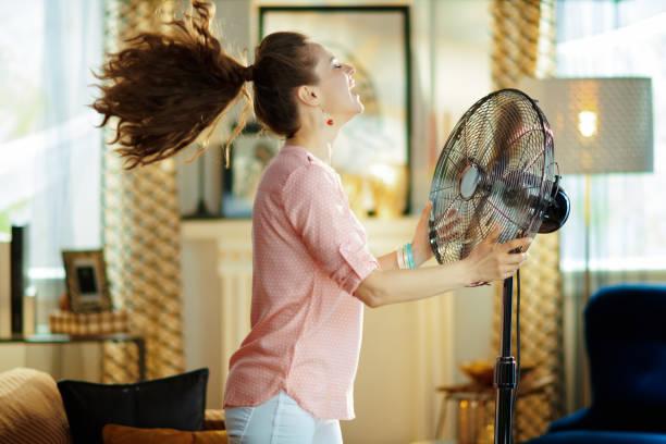 ama de casa sonriente disfrutando de aire fresco en frente del ventilador de trabajo - calor fotografías e imágenes de stock