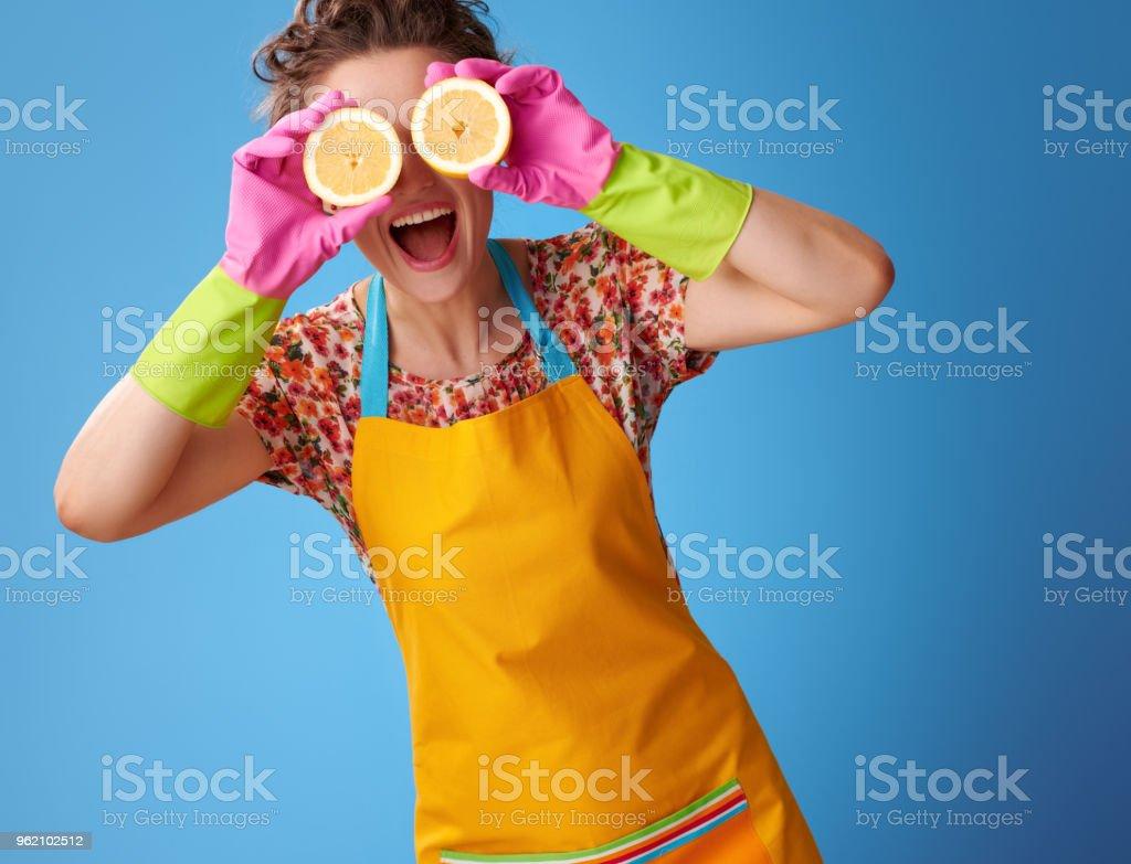 lächelnde Hausfrau Holding halben Zitrone vor Augen auf blau – Foto