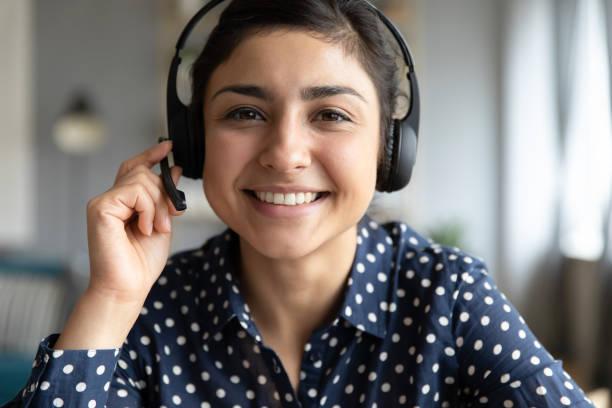 glimlachend indisch meisje professioneel dragen headset blik op camera webcam - dienstverlening stockfoto's en -beelden