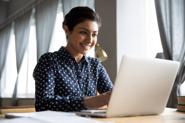 Smiling indian girl student professional typing on laptop at table Smiling indian girl student professional employee typing on laptop sit at home office table, happy hindu woman studying e learning online software using technology app for work education concept professional woman stock pictures, royalty-free photos & images