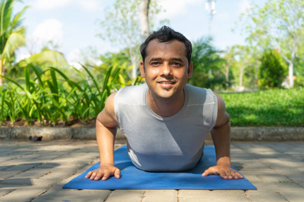 Smiling Indian man doing cobra pose outdoors in park Smiling Indian man doing cobra pose outdoors in park with green plants in background. Outdoor yoga concept. Front view. cobra pose stock pictures, royalty-free photos & images