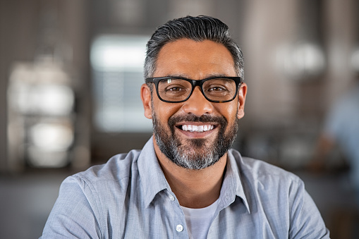 Smiling mature indian man wearing spectacles and looking at camera. Portrait of middle eastern confident businessman at office. Portrait of successful mid entrepreneur feeling satisfied and working from home.