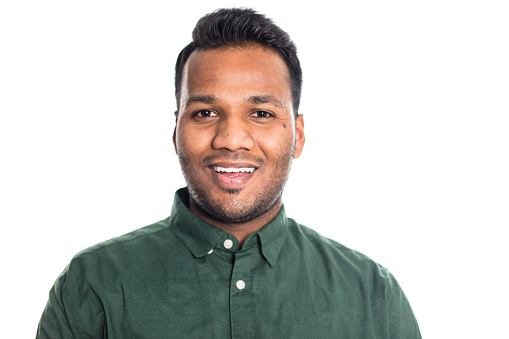 Portrait of smiling Indian man looking at camera. Happy male wearing a shirt on white background.