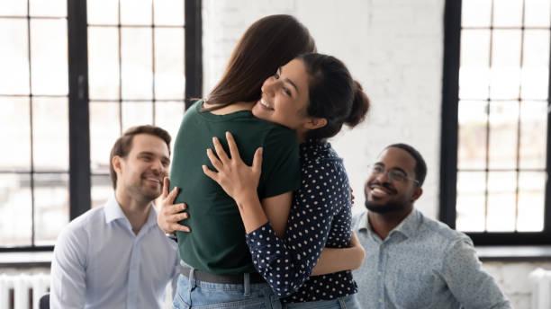 smiling indian psychologist hugging patient at group counselling session - empatia imagens e fotografias de stock
