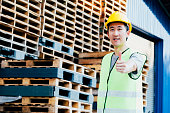 istock Smiling industrial logistics worker with hard helmet in facilities with thumbs up 1159060800