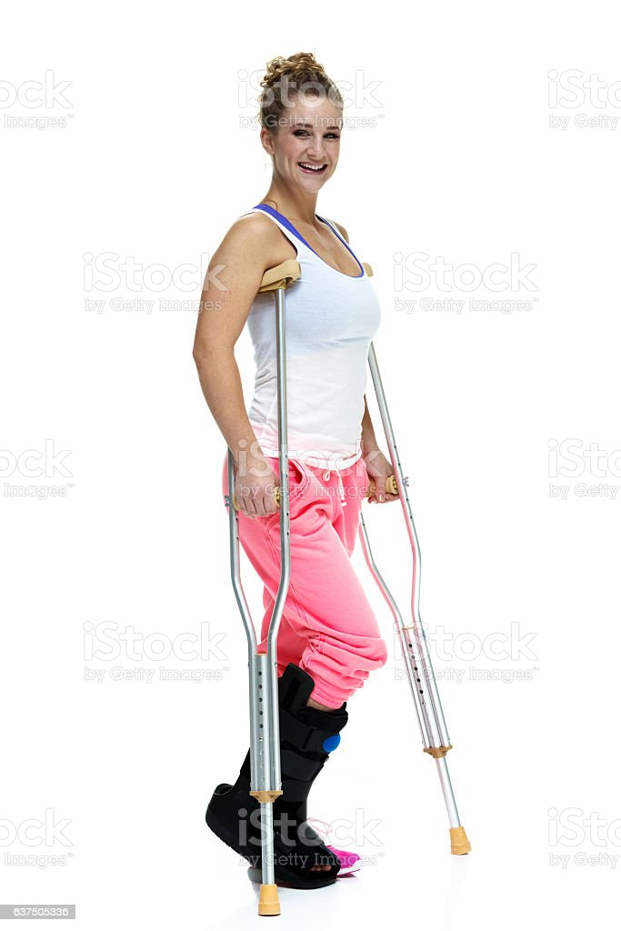 Smiling injured sports woman walking with crutches - Photo