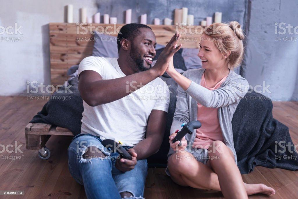 Smiling international couple amusing at home stock photo