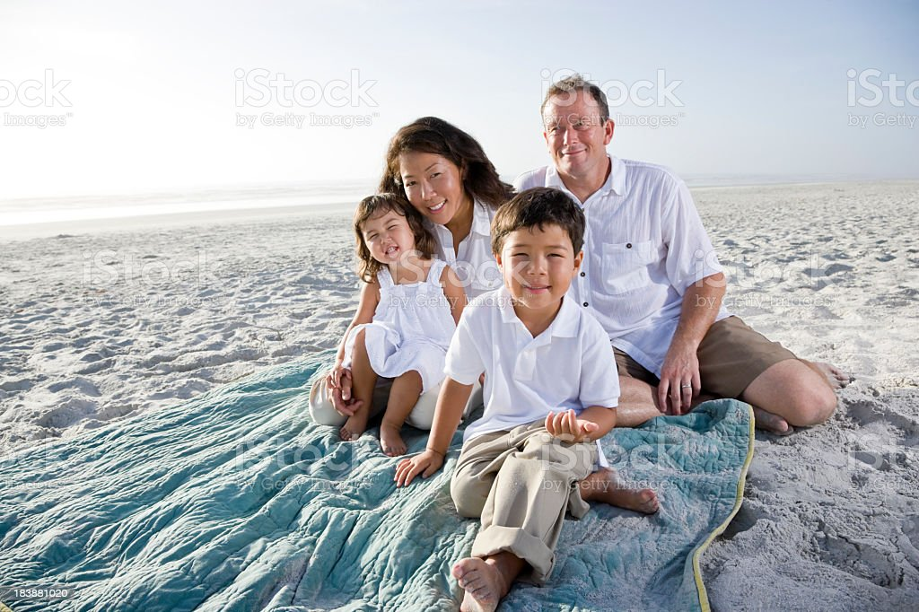 Smiling interracial family sitting on beach royalty-free stock photo