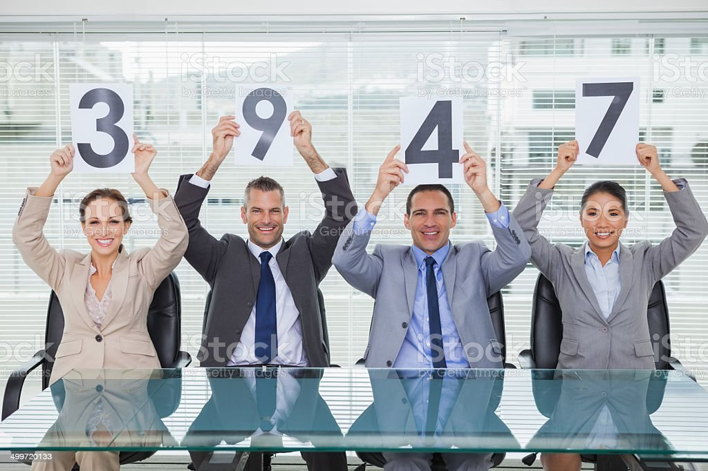 Smiling interview panel holding signs giving grade to their appl stock photo