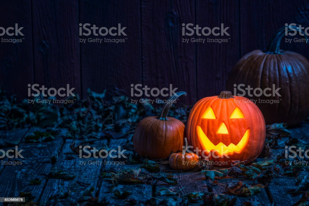 Smiling Jack O' Lantern on old wooden porch in the moon light stock photo