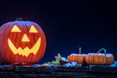 A pumpkin carved into a smiling Jack O' Lantern sitting on an old wooden porch with small pumpkins and fallen leaves as a Halloween decoration. It is glowing from the light within and accented by the blue moon light.