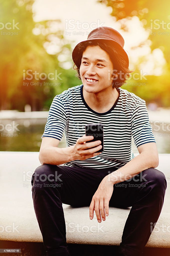 Smiling japanese teenager with smart phone stok fotoğrafı
