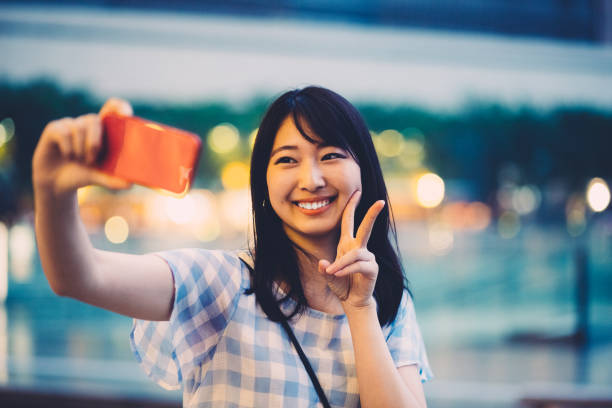 smiling japanese woman taking selfie - self portrait photography stock pictures, royalty-free photos & images