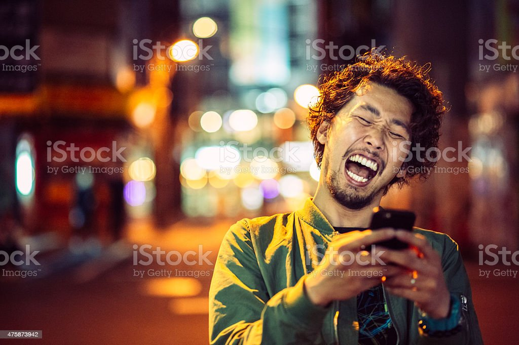 Smiling japanese young man with smart phone at night urban stock photo