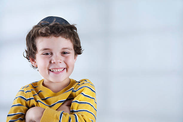 Smiling Jewish boy in striped yellow shirt A young Jewish boy wearing a yarmulke, looking at the camera. judaism stock pictures, royalty-free photos & images