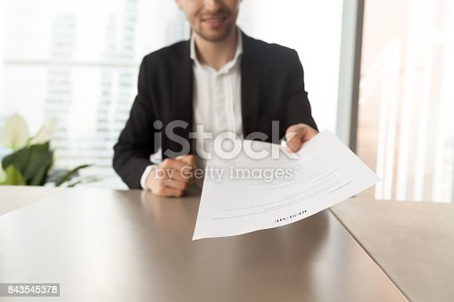 smiling job applicant handing over resume to recruiter during