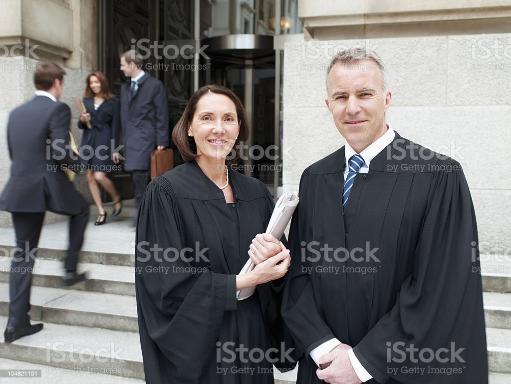 Smiling judges in robes standing outside courthouse stock photo