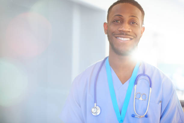 Smiling junior doctor in blue scrubs A young black junior doctor smiles to camera on ward in a hospital anesthesiologist stock pictures, royalty-free photos & images