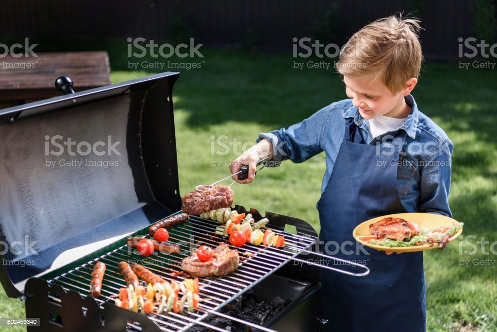 smiling kid boy in apron preparing tasty stakes on barbecue grill outdoors stock photo